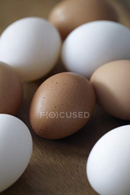 Крупным планом вид кучи белые и коричневые яйца на деревенский деревянный столик — стоковое фото