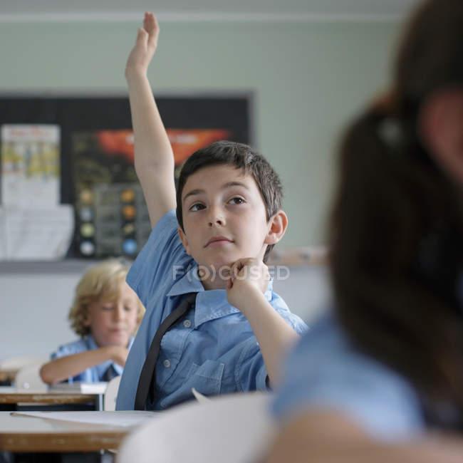 Écolier levant la main — Photo de stock