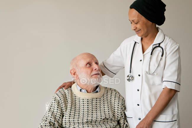 Смотритель улыбается пожилому человеку, сосредоточьтесь на переднем плане — стоковое фото