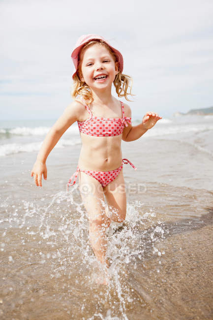 Smiling girl playing in waves on beach — Stock Photo