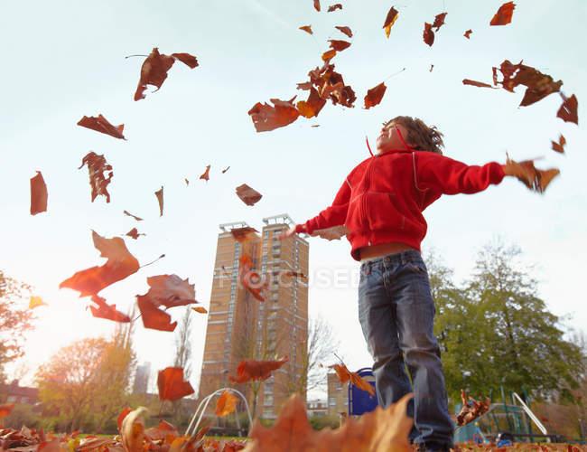 Niño jugando con hojas de otoño - foto de stock