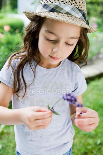 Девушка осматривает цветы на открытом воздухе — стоковое фото