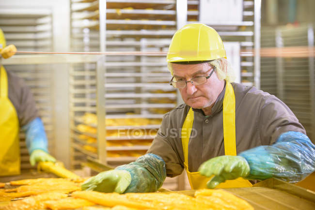 Worker preparing haddock fish for smoking in food factory — Stock Photo