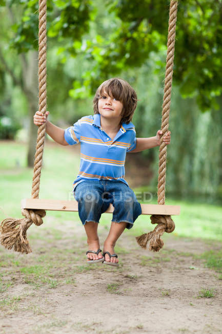 Посміхаючись хлопчик сидить у дереві гойдалки — стокове фото