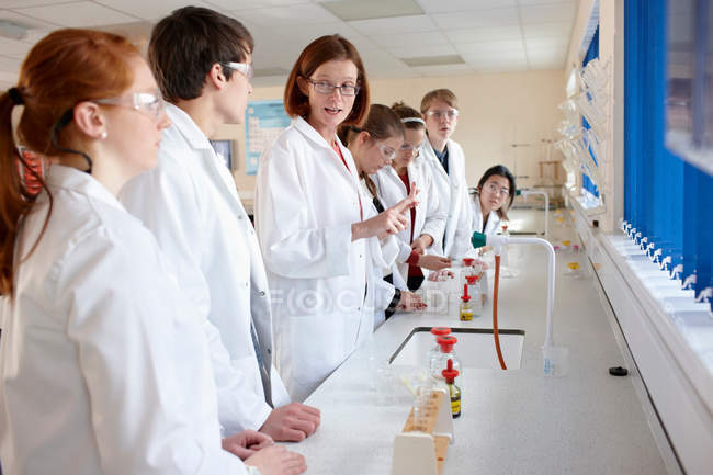 Students and teacher in chemistry lab — Stock Photo