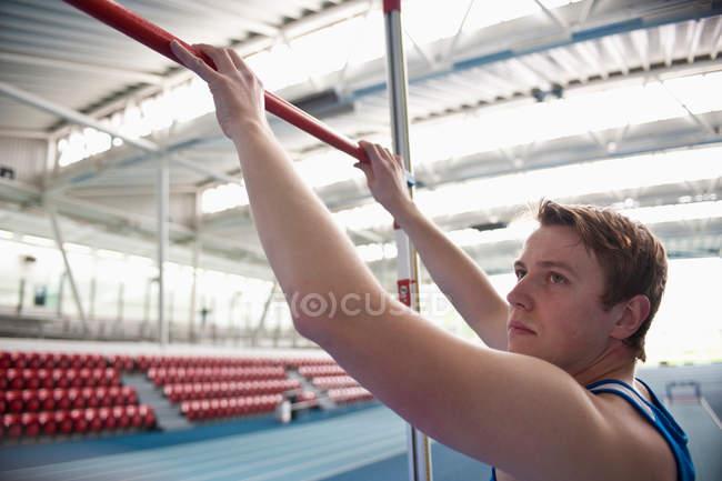 Atleta masculino definir barra de salto alto — Fotografia de Stock