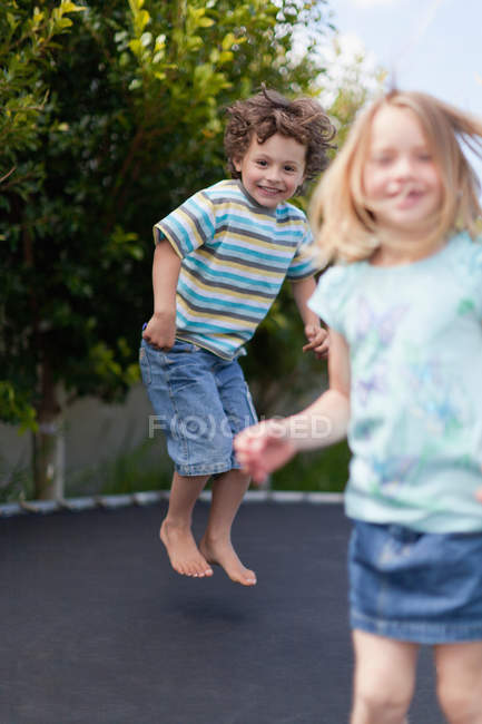 Smiling children jumping on trampoline, selective focus — Stock Photo