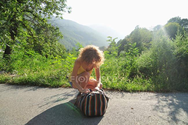 Женщина закрывает рюкзак на сельской дороге — стоковое фото