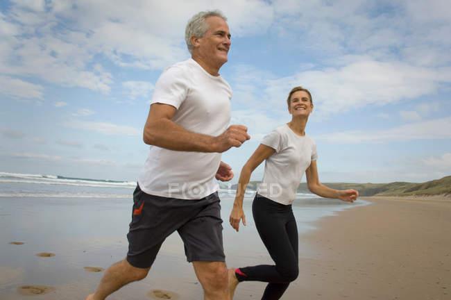 Paar läuft am Strand — Stockfoto