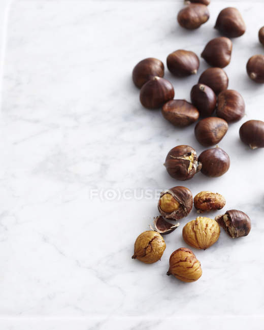 Fresh chestnuts on marble table — Stock Photo