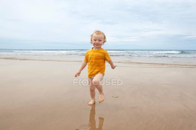 Мальчик ходит волнами по пляжу — стоковое фото