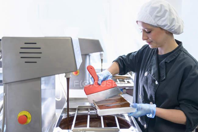 Chocolatier füllt Schokoladenformen in Schokoladenfabrik — Stockfoto