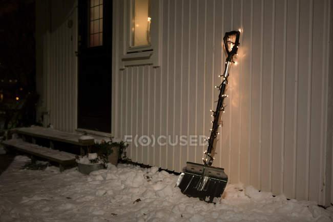 Pala adornados con luces de hadas en la nieve cerca de la casa - foto de stock