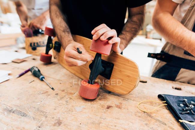 Чоловіків в майстерні кріплення коліс на скейтборд — стокове фото