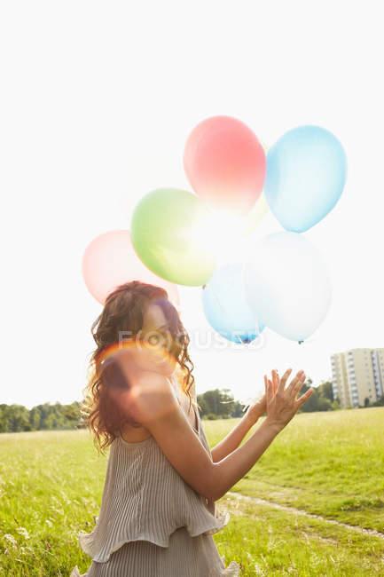 Femme avec des ballons à air dans les prairies — Photo de stock