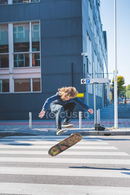 Young male urban skateboarder doing skateboard jump on pedestrian crossing — Stock Photo