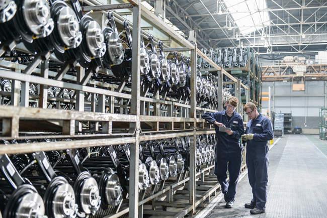Рабочие проверяют большое количество осей на стеллажах на автозаводе — стоковое фото