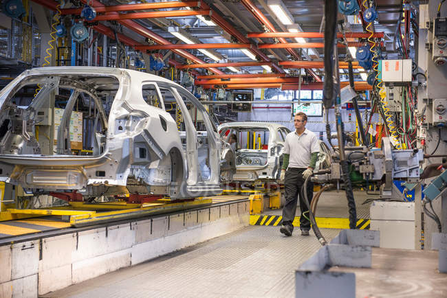 Workers with car bodies on production line in car factory — Stock Photo