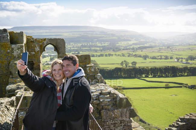 Пара фотографирующая себя на стенах замка Болтон с видом на Венсли под высоким углом. Здание 1-го класса XIV века, памятник древности — стоковое фото