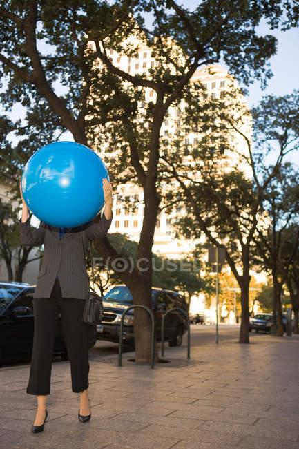 Vue de face de la femme d'affaires tenant un ballon bleu — Photo de stock