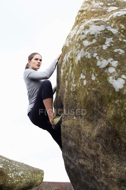 Rock climber scaling boulder — Stock Photo