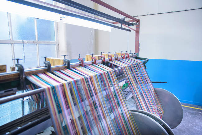 Multicoloured threads on industrial loom in textile mill — Stock Photo