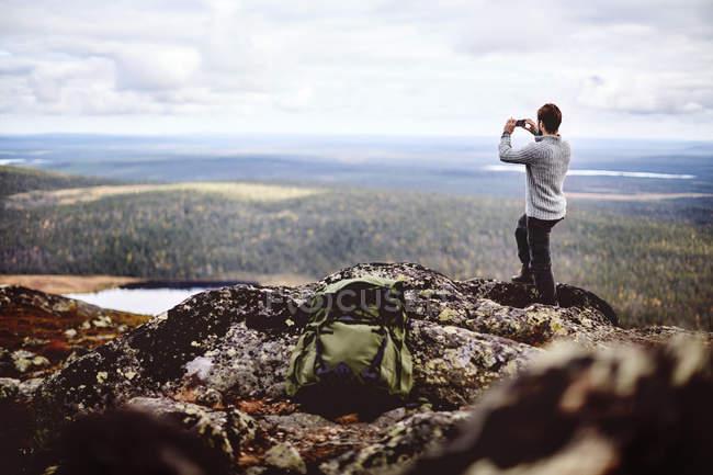Hiker taking photo on cliff top, Keimiotunturi, Lapland, Finland — стоковое фото