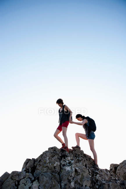 Hikers helping each other climb rock against blue sky — Stock Photo