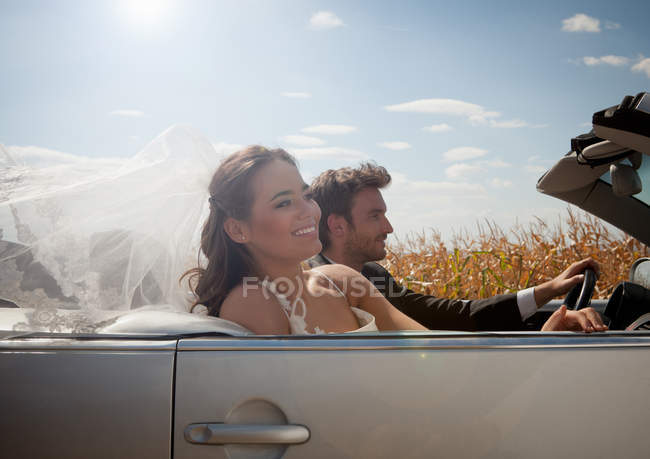 Newlywed couple driving in convertible — Stock Photo