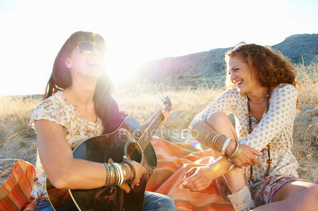 Women playing guitar in grass — Stock Photo