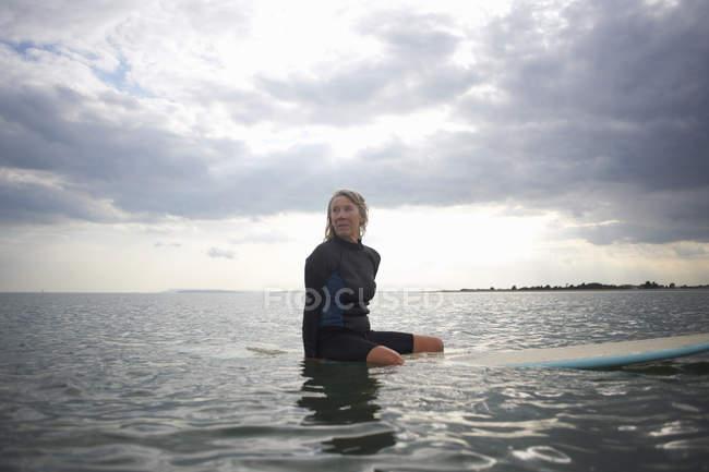 Mulher sênior sentada na prancha de surf no mar — Fotografia de Stock