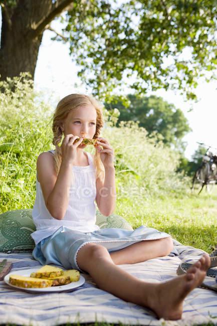 Sitzendes Mädchen essen Ananas — Stockfoto