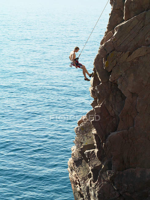 Rock climber rappelling down rock face — Stock Photo