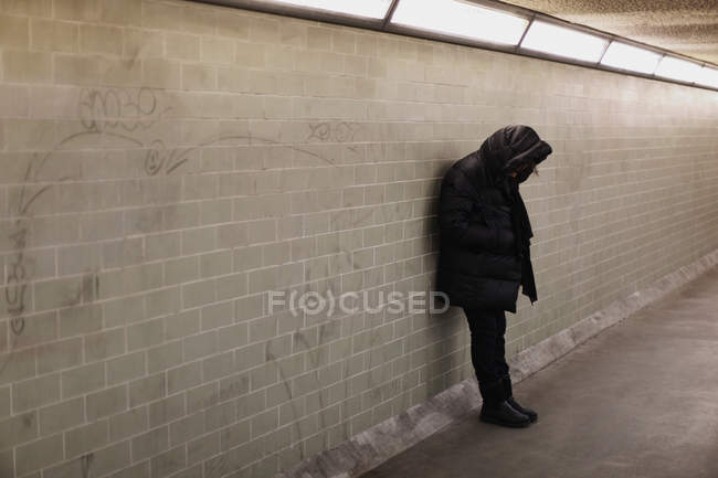 Pessoa encapuzada apoiada na parede do metrô — Fotografia de Stock