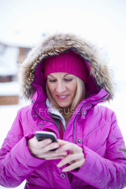Donna che utilizza il telefono cellulare in inverno — Foto stock