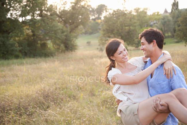 Мужчина, несущий подружку в пшеничном поле — стоковое фото