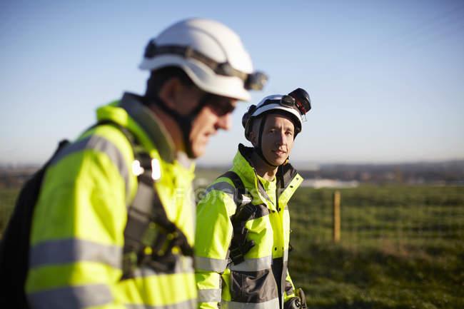 Deux ingénieurs sur le chantier de construction d'un parc éolien marchent ensemble — Photo de stock