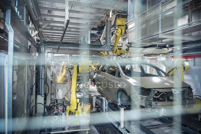 Robots appliquant un mastic sur les voitures — Photo de stock