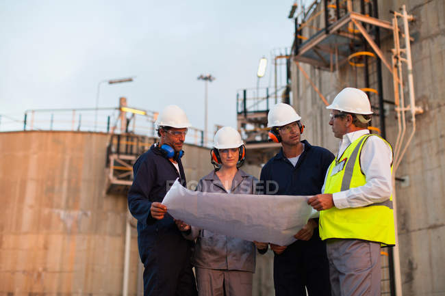 Workers reading blueprints at plant — Stock Photo
