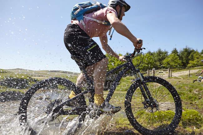 Велогонщики ездят по воде — стоковое фото
