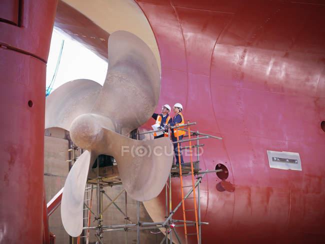 Робітники перевірки нижньої частини судна в сухий док — стокове фото