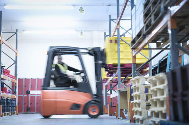 Blurred motion of man in industrial training with forklift truck in warehouse — Stock Photo
