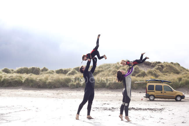 Parents lifting sons on beach — Stock Photo