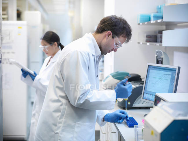Scientists conducting the process of Polymerase chain reaction (PCR) to amplify DNA by using a thermocycler to create samples — Stock Photo