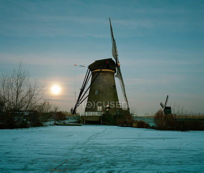 Molino de viento rural en el río congelado - foto de stock