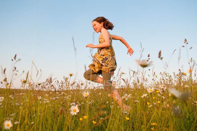 Девушка, бегущая по полю цветов, избирательный фокус — стоковое фото