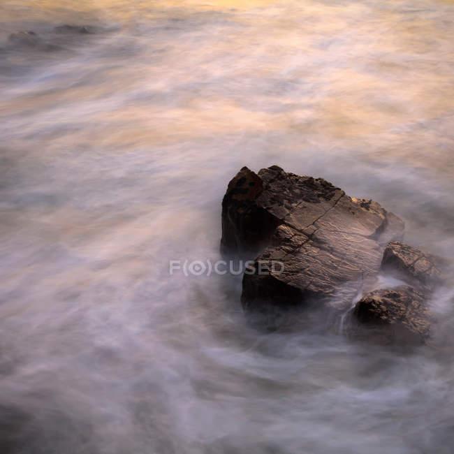 Roccia in mare a tempo nebbioso — Foto stock