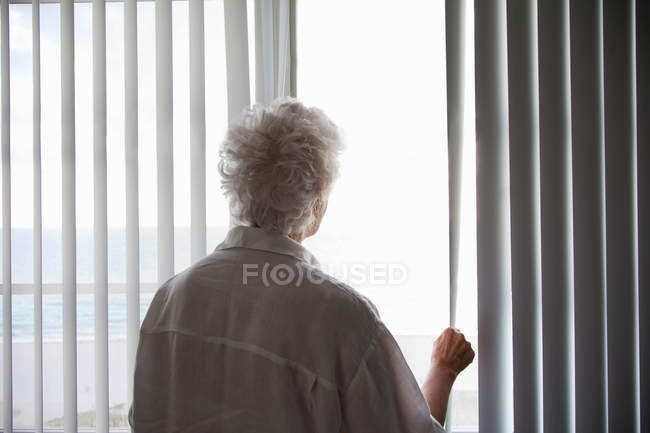 Back view of Senior Woman looking out of a window — Stock Photo