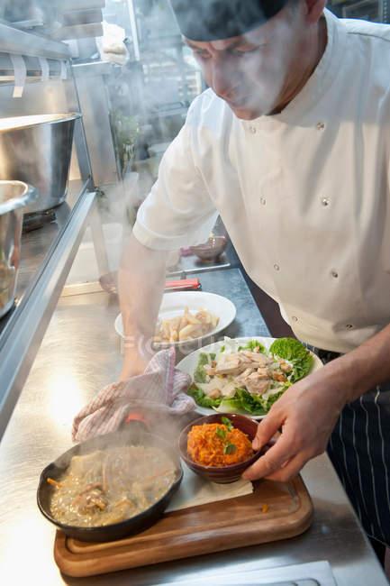 Chef preparazione piatti di cibo in cucina — Foto stock