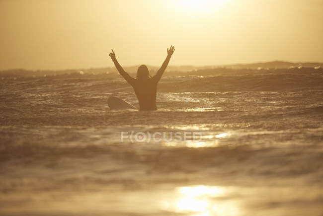 Силуэт молодого серфера с поднятыми в море руками, Девон, Англия, Великобритания — стоковое фото